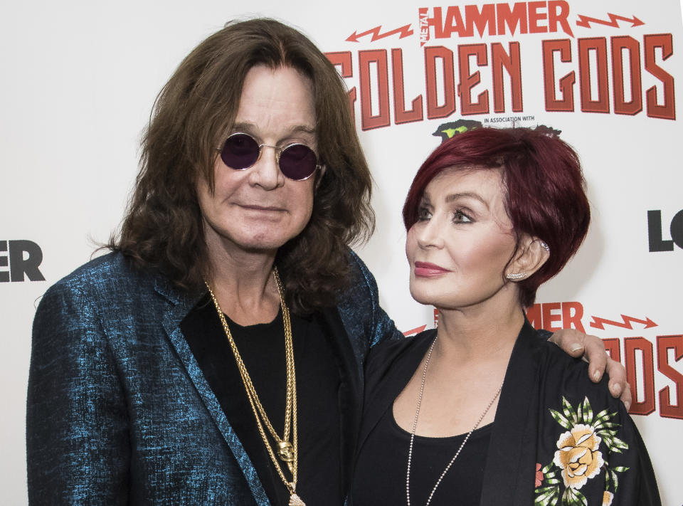 """FILE - This June 11, 2018 file photo shows musician Ozzy Osbourne, left, and his wife Sharon Osbourne at the Metal Hammer Golden God awards in London. The 71-year-old Grammy winner and former vocalist for the metal band Black Sabbath said during an interview on """"Good Morning America"""" that aired Tuesday, Jan. 21, 2020, that he's been diagnosed with Parkinson's disease, a nervous system disorder that affects movement.  The diagnosis came after a fall last year.  (Photo by Vianney Le Caer/Invision/AP, File)"""