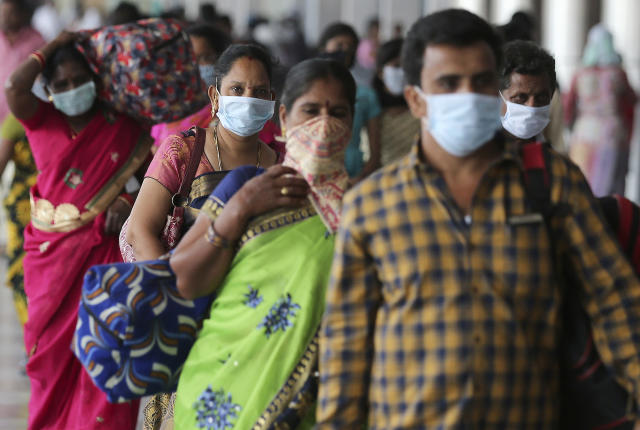 Indian passengers wear face masks as a precaution against COVID-19 arrive at Secunderabad Railway Station in Hyderabad, India, Saturday, March 21, 2020. For most people, the new coronavirus causes only mild or moderate symptoms. For some it can cause more severe illness. (AP Photo/Mahesh Kumar A.)