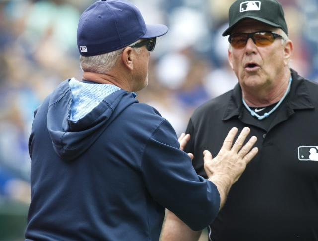 Tampa Bay Rays manager Joe Maddon argues with umpire Bob Davidson after a call at first base was reviewed and overturned in the Toronto Blue Jays favor during fourth inning of a baseball game in Toronto, Saturday, Aug. 23, 2014. (AP Photo/The Canadian Press, Fred Thornhill)