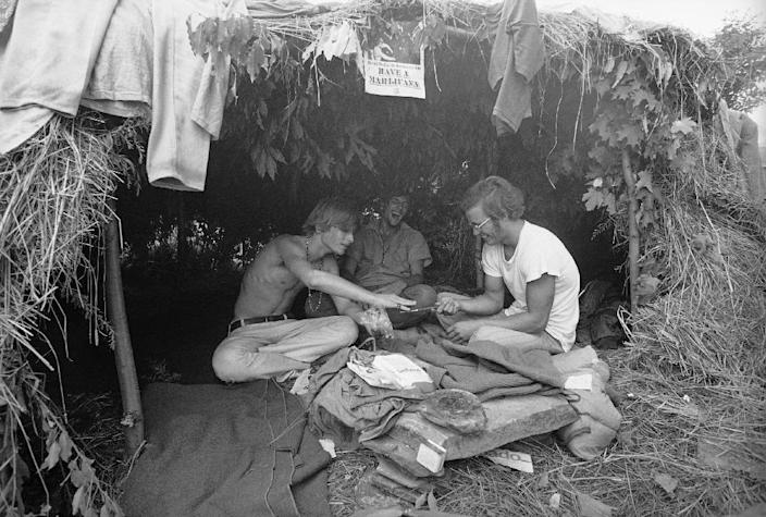 """FILE - This Aug. 17, 1969 black-and-white file photo shows music fans seeking shelter is a grass hut at the Woodstock Music and Art Festival in Bethel, N.Y. where the sign above reads """"Have a Marijuana."""" It took 50 years for American attitudes about marijuana to zigzag from the paranoia of """"Reefer Madness"""" to the excesses of Woodstock back to the hard line of Just Say No. And now, in just a few short years, public opinion has shifted so dramatically toward pragmatic acceptance of marijuana that even those who champion legalization are surprised at how quickly attitudes are changing and states are moving to approve the drug for medical use and just for fun. (AP Photo, File)"""