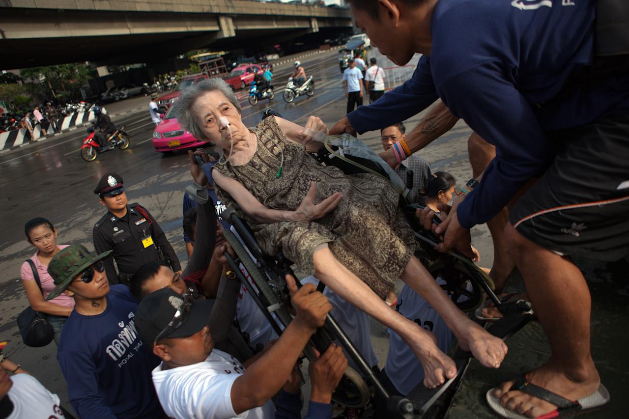 BANGKOK, THAILAND - OCTOBER 26: An elderly woman gets put on a truck going toward a hospital down the newly flooded streets near the Chao Phraya river October 26, 2011 in Bangkok, Thailand. Hundreds of factories closed in the central Thai province of Ayutthaya and Nonthaburi as the flood waters began to reach Bangkok. Around 350 people have died in flood-related incidents since late July according to the Department of Disaster Prevention and Mitigation, with Thailand experiencing the worst flooding in 50 years.  (Photo by Paula Bronstein/Getty Images)