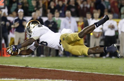 Notre Dame running back Theo Riddick dives across the goal line to score a touchdown during the first half of an NCAA college football game against USC on Saturday, Nov. 24, 2012, in Los Angeles. (AP Photo/Danny Moloshok)