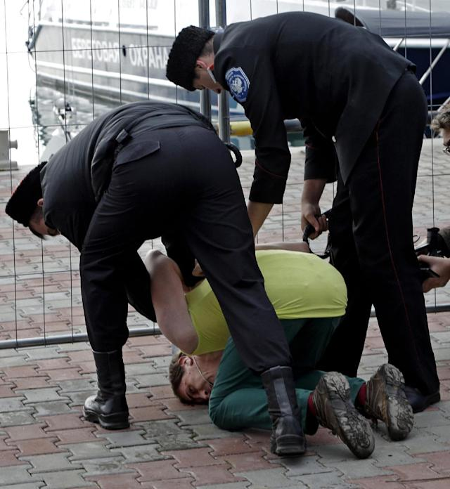 A member of the punk group Pussy Riot is restrained by Cossack militia after the group tried to perform in Sochi, Russia, on Wednesday, Feb. 19, 2014. The group had gathered in a downtown Sochi restaurant, about 30km (21miles) from where the Winter Olympics are being held. They left the restaurant wearing bright dresses and ski masks and had only been performing for a few seconds when they were set upon by Cossacks. (AP Photo/Morry Gash)