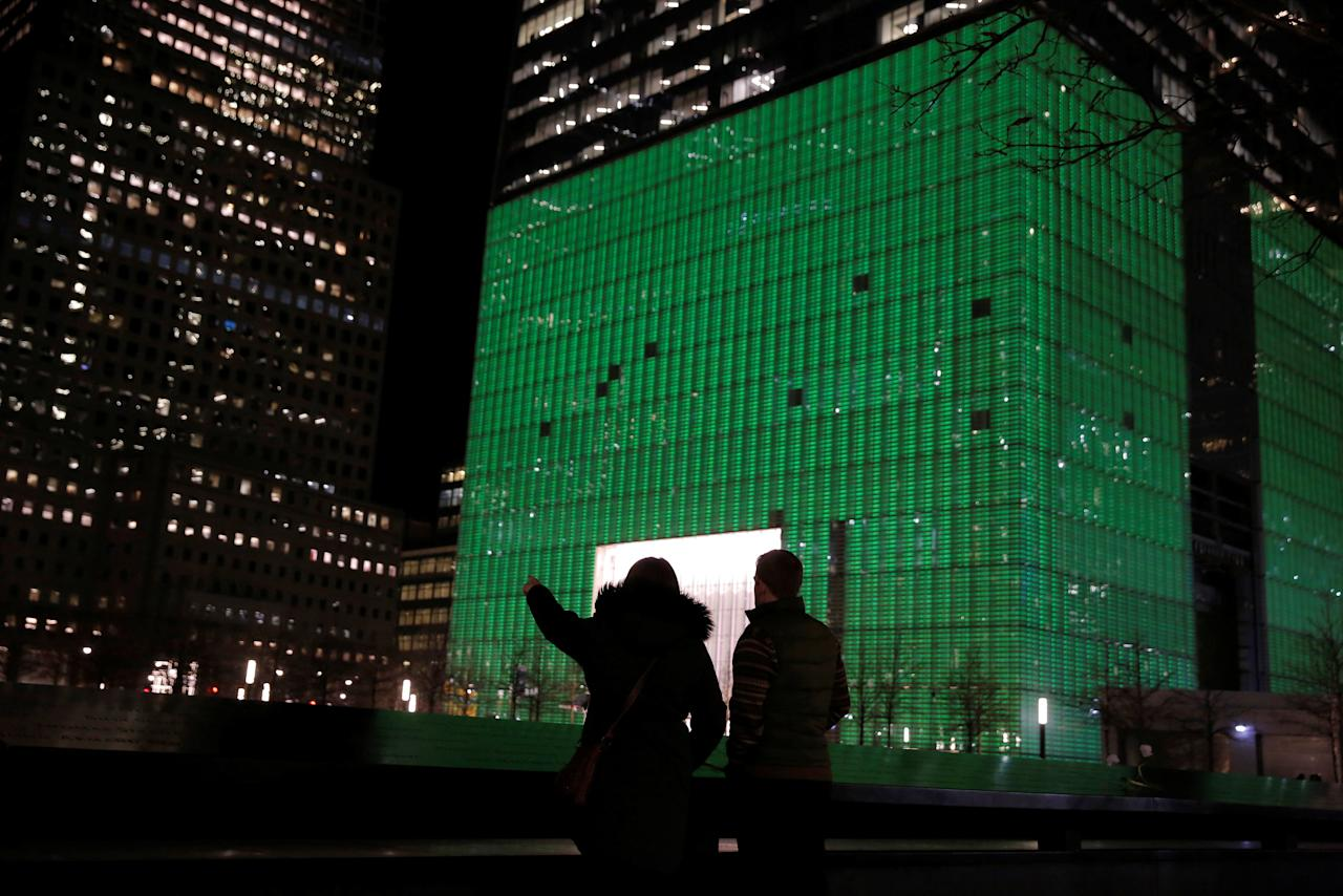 Visitors to the National September 11 Memorial and Museum stand in front of One World Trade Center, which was lit green for St. Patrick's day, in Manhattan, New York, U.S., March 17, 2017.  REUTERS/Andrew Kelly