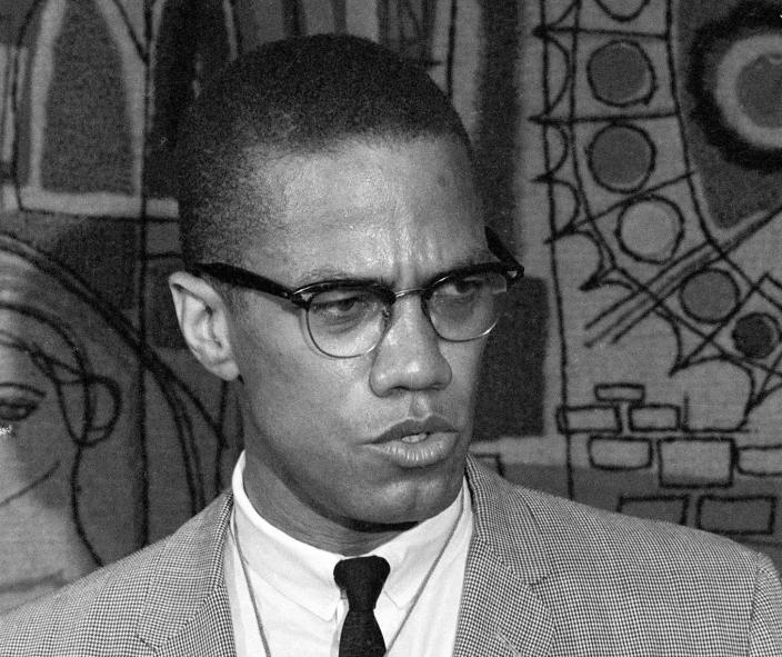 """FILE - This March 12, 1964 file photo, Malcolm X addresses reporters at the Hotel Park-Sheraton in New York. Malcolm X's family and estate said rapper-singer Nicki Minaj's use of the black nationalist with a rifle in his hands, juxtaposed with a racial slur, for her single artwork is disrespectful and offensive. In an exclusive statement to The Associated Press on Friday, Feb. 14, 2014, Malcolm X's daughter, Ilyasah Shabazz, said Minaj's use of the picture is """"in no way is endorsed by my family."""" (AP Photo, File)"""