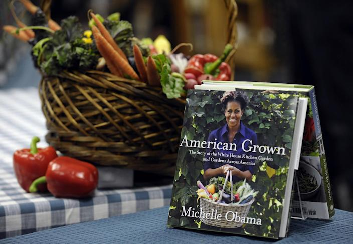 """FILE - This May 7, 2013 file photo shows copies of the book by first lady Michelle Obama """"American Grown: The Story of the White House Kitchen Garden and Garden Across America,"""" displayed at the Politics & Prose bookstore in Washington where she signed copies of her book.By reaching beyond the pair of relatively safe issues she has pushed _ reducing childhood obesity and rallying public support for military families _ the Harvard-trained lawyer who some say has played it safe is showing a willingness to step outside of her comfort zone. (AP Photo/Susan Walsh)"""
