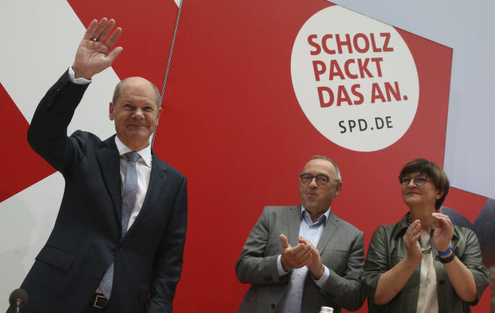 German Social Democratic Party, SPD, party leaders Saskia Esken, right, and Norbert Walter-Borjans, center, applaud to the party's candidate for chancellery Olaf Scholz as he arrives at the meeting of the SPD Federal Executive Committee in Berlin, Germany, Monday, Sept. 27, 2021. Following Sunday's election leaders of the German parties were meeting Monday to digest a result that saw Merkel's Union bloc slump to its worst-ever result in a national election and appeared to put the keys to power in the hands of two opposition parties. Both Social Democrat Olaf Scholz and Armin Laschet, the candidate of Merkel's party, laid a claim to leading the next government. (Wolfgang Kumm/dpa via AP)