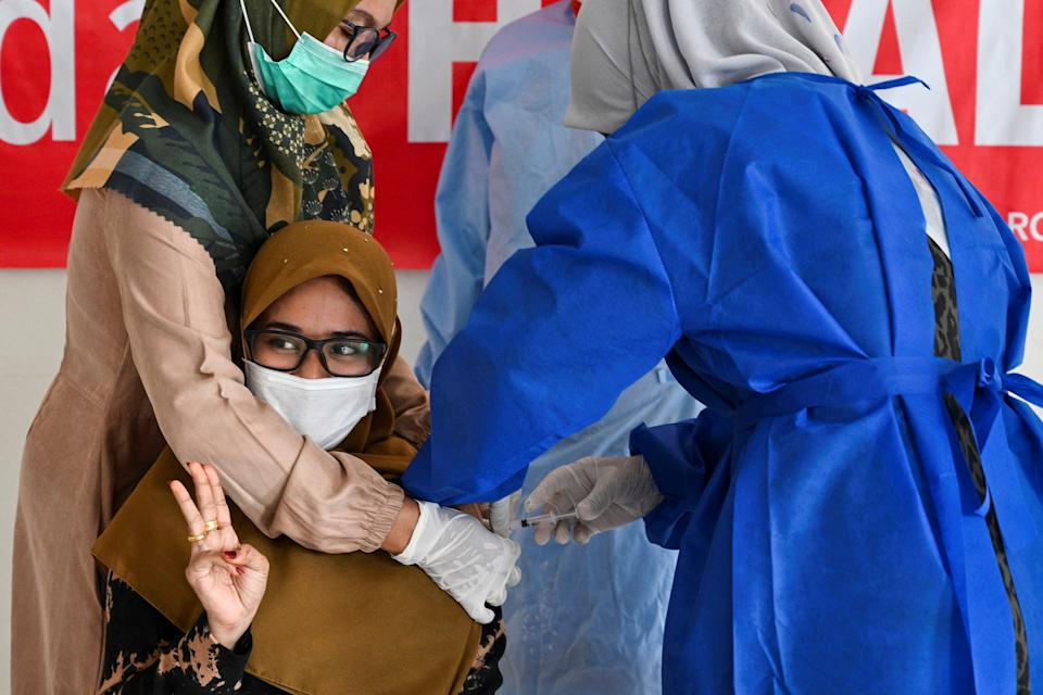 TOPSHOT - A woman receives a dose of the Moderna Covid-19 vaccine, donated to Indonesia by the US, during a booster vaccination drive in Barona Jaya on the outskirts of Banda Aceh on August 13, 2021. (Photo by CHAIDEER MAHYUDDIN / AFP) (Photo by CHAIDEER MAHYUDDIN/AFP via Getty Images)
