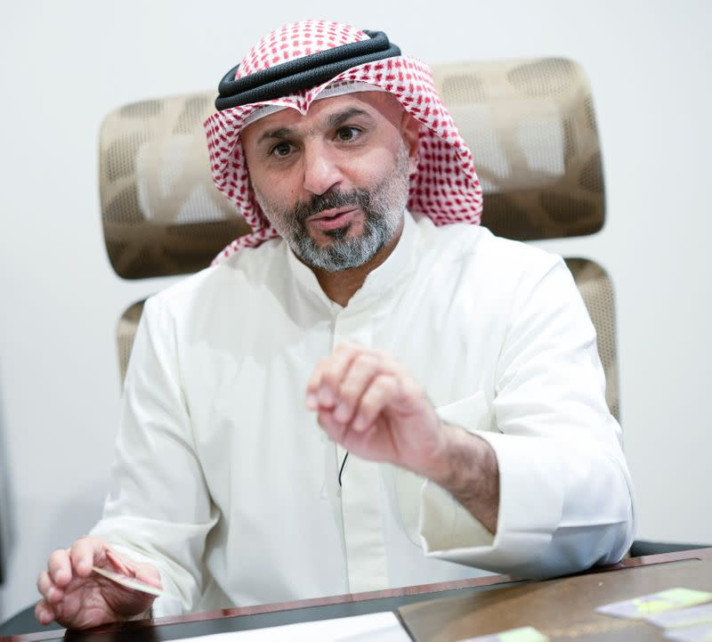 Tarik al Baijan, Director of Cards at the Central Agency for Remedying Illegal Residents Status gestures during an interview with Reuter,s in Ardiya