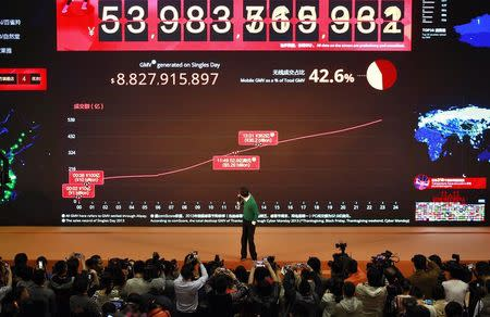 """Alibaba Group Executive Chairman Jack Ma looks back at a giant electronic screen showing real-time sales figures of the company's Taobao.com and Tmall.com, on the """"Singles' Day"""" online shopping festival, at the company headquarters in Hangzhou, Zhejiang province November 11, 2014. REUTERS/Stringer"""