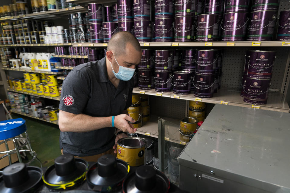 Billy Wommack, purchasing director at the W.S. Jenks & Sons hardware, carries a gallon of paint to a shaker at the mixing station of the hardware store's paint department, Friday, Sept. 24, 2021, in northeast Washington. The chemical shortages, and a near doubling of oil prices in the past year, mean higher prices for many goods. The W.S. Jenks & Son hardware store is only getting 20% to 30% of paint it needs to meet customer demand without backordering; in normal times the so-called fill rate usually runs 90%. (AP Photo/Manuel Balce Ceneta)