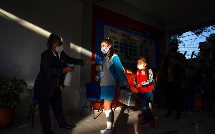 A girl is sanitised as she enters a school during the resumption of face-to-face classes in Mexico City on June 7 - AFP