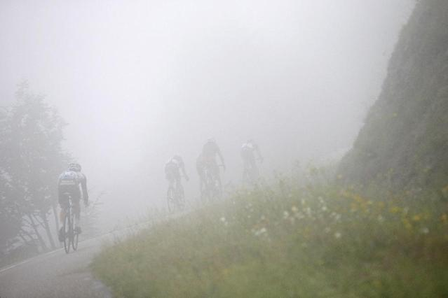 10ThingstoSeeSports - France's Christophe Riblon, rear, Switzerland's Marcel Wyss, second left, and France's Amael Moinard, front, ride through the fog during the tenth stage of the Tour de France cycling race over 161.5 kilometers (100.4 miles) with start in Mulhouse and finish in La Planche des Belles Filles, France, Monday, July 14, 2014. (AP Photo/Laurent Cipriani, File)