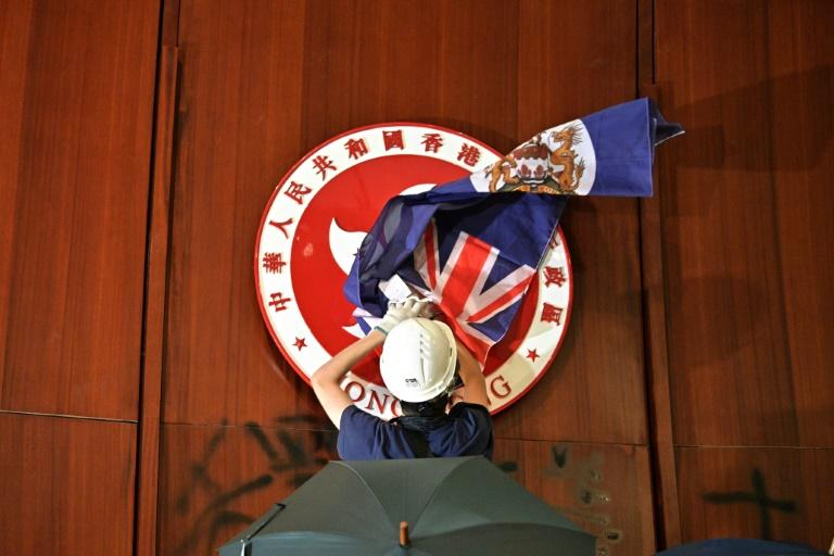 Protesters unfurled the colonial-era flag and defaced the Hong Kong crest after breaking into the legislative council building (AFP Photo/Anthony WALLACE)