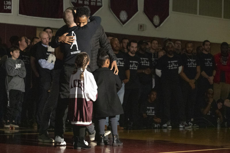 Kobe Bryant's cousin, John Cox, top right, is hugged by Lower Merion Coach Gregg Downer  during a ceremony at Lower Merion High School, Saturday, Feb. 1, 2020, in Ardmore, Pa. The school paid tribute to Bryant, his daughter and the seven other victims of a helicopter crash in California. (Charles Fox/The Philadelphia Inquirer via AP)