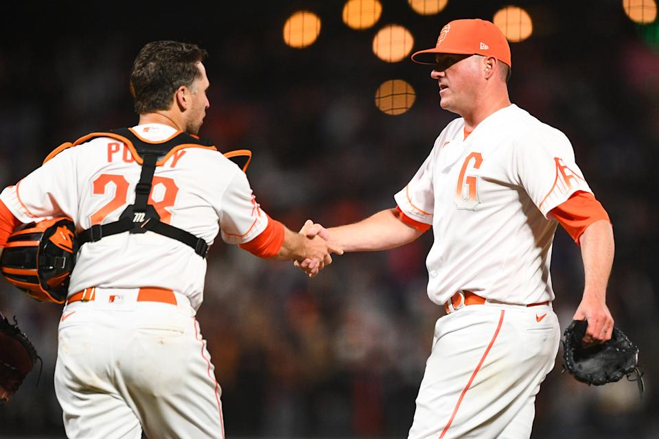 San Francisco Giants pitcher Jake McGee (17) shakes San Francisco Giants catcher Buster Posey's hand after the Giants' win on Tuesday. (Photo by Brian Rothmuller/Icon Sportswire via Getty Images)