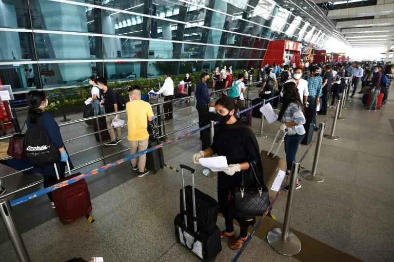At New Delhi airport, hundreds of people anxious to get home but apprehensive about the risks queued from before dawn (AFP Photo/Money SHARMA)