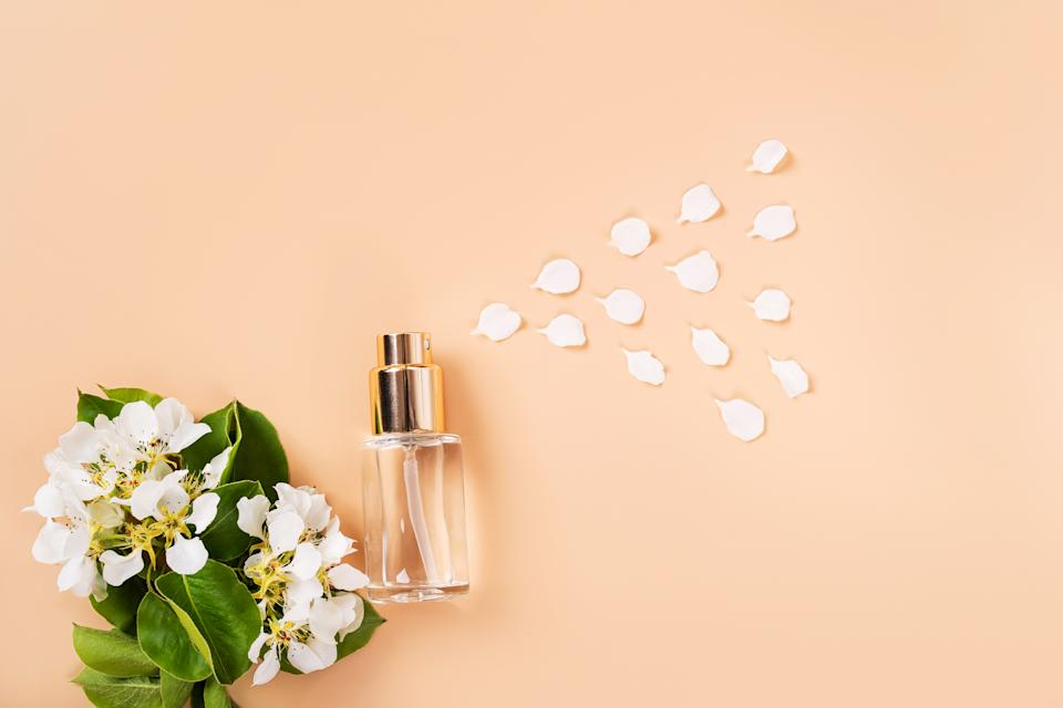 Glass transparent bubble with liquid and flowering cherry twigs on a pastel peach pink delicate background.  Anti-aging facial skin care and bodies for summer sun