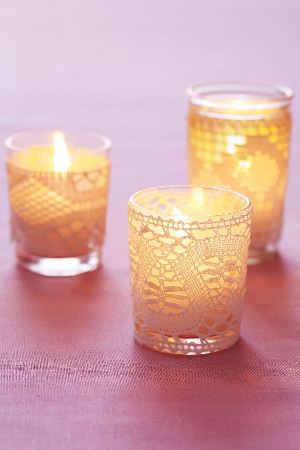 <p>Lacey candle holders make for a soft and beautiful Valentine's Day gift. Just picture 20 of these scattered around a room — perfectly romantic, no? To make, simply glue lace to clear glass votives. </p>