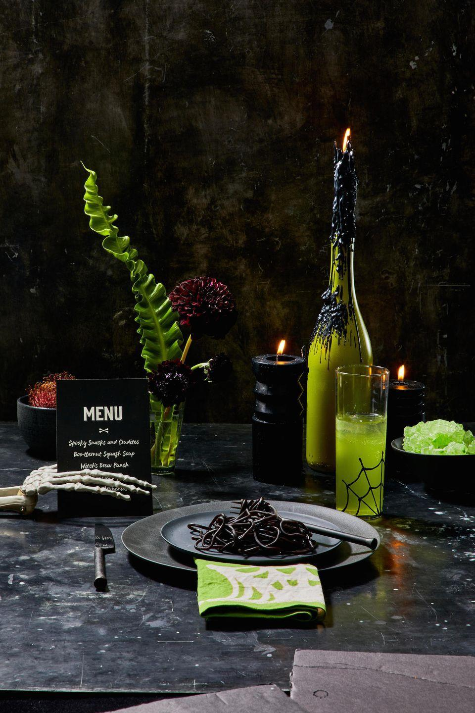 <p>Combine dark plates with bright accents for a tablescape that'll spook (and delight!) your guests. Be sure to place menus in skeleton hands and serve festive foods in colors like black and green. </p>