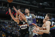 Denver Nuggets forward Mason Plumlee reaches for a rebound near Charlotte Hornets center Willy Hernangomez (9) and Nuggets forward Juan Hernangomez, right, during the first half of an NBA basketball game Wednesday, Jan. 15, 2020, in Denver. (AP Photo/David Zalubowski)