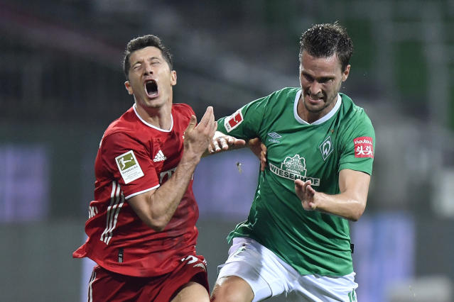 Bayern's Robert Lewandowski, left, fights for the ball with Bremen's Sebastian Langkamp during the German Bundesliga soccer match between Werder Bremen and Bayern Munich in Bremen, Germany, Tuesday, June 16, 2020. Because of the coronavirus outbreak all soccer matches of the German Bundesliga take place without spectators. (AP Photo/Martin Meissner, Pool)