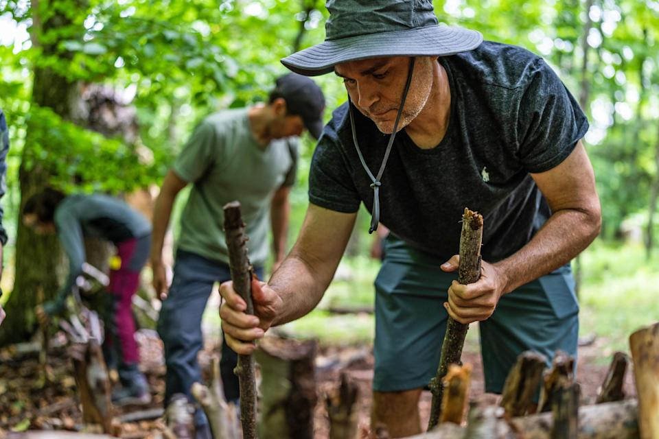 David D'Alessio, from Harlem, New York City, helps to build a debris hut shelter at the Mountain Scout Survival School. (Michael Rubenstein / for NBC News)