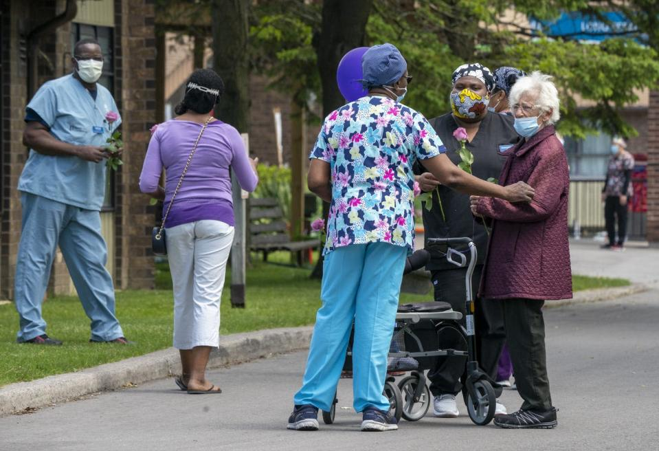 Long-term care workers talk outside to an elderly woman; all wear masks.