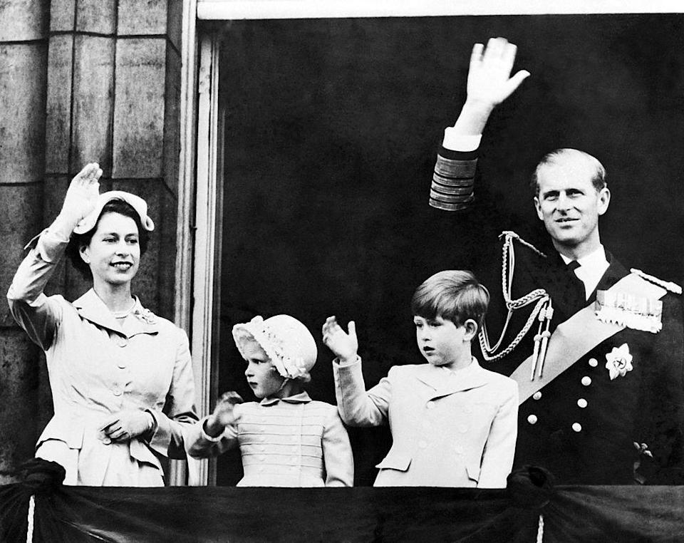 <p>Queen Elizabeth II, Prince Philip, Prince Charles, and Princess Ann salute the crowd from the balcony at Buckingham Palace following a trip around the world.</p>