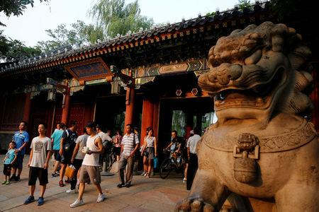 FILE PHOTO: People enter and leave the gate of Peking University in Beijing