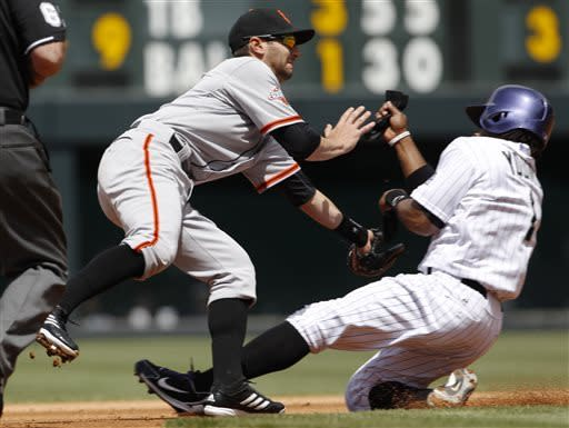 San Francisco Giants second baseman Nick Noonan, left, tries to field the throw as Colorado Rockies' Eric Young steals second base in the first inning of the MLB National League baseball game in Denver on Sunday, May 19, 2013. (AP Photo/David Zalubowski)