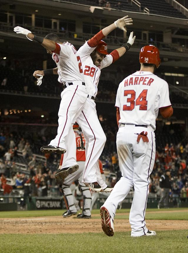 Washington Nationals Jayson Werth (28) celebrates scoring the wining run, with teammates Ian Desmond (20) and Bryce Harper (34), on a single hit by Adam LaRoche during the ninth inning of a baseball game against the Los Angeles Angels, Wednesday, April 23, 2014 in Washington. The Nationals won 5-4. (AP Photo/Pablo Martinez Monsivais)
