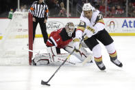 New Jersey Devils goaltender Keith Kinkaid, left, keeps watch as Vegas Golden Knights right wing Ryan Reaves (75) controls the puck during the first period of an NHL hockey game, Friday, Dec. 14, 2018, in Newark. (AP Photo/Julio Cortez)