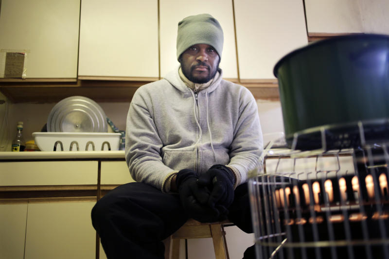 In this Jan. 27, 2013 photo, Devon Lawrence poses for a picture in his kitchen, which is currently heated by a kerosene heater and his stove top, in the Far Rockaway neighborhood of New York. Lawrence hasn't had working heat since Superstorm Sandy's floodwaters destroyed the oil burner in the basement. Three months after Sandy struck, thousands of storm victims in New York and New Jersey are stuck in limbo. Waiting for the heat to come on, for insurance money to come through, for loans to be approved. Waiting, in a broader sense, for their upended lives to get back to normal. (AP Photo/Seth Wenig)
