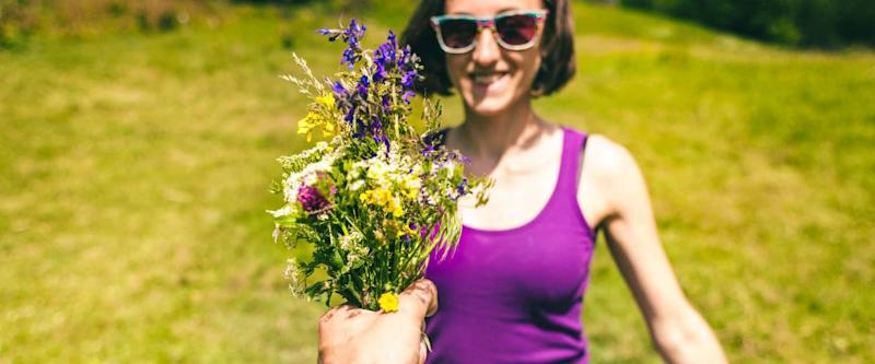 The man holds out a bouquet of wild flowers to the woman. A gift for a girl. The smiling brunette is standing in a meadow. Violet flowers in female hands. Date.