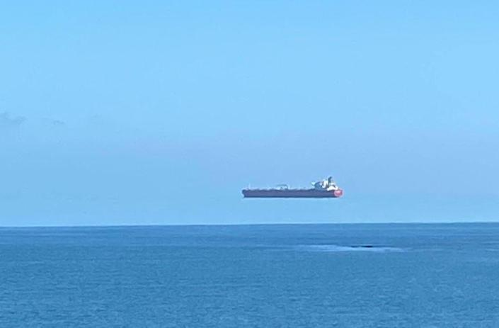 A ship appears to hover over the sea off the coast of Cornwall, England. / Credit: David Morris/APEX