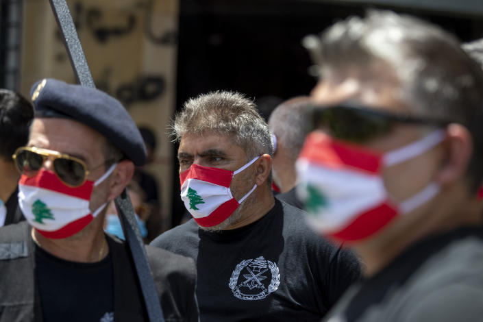 Anti-government protesters shout slogans while wearing masks with the colors of the Lebanese flag, to help curb the spread of the coronavirus, in front of the Ministry of Economy, in downtown Beirut, in Beirut, Lebanon, Monday, May 18, 2020. (AP Photo/Hassan Ammar)