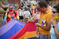 A child holds on to a large rainbow flag during the Bucharest Pride 2021 in Bucharest, Romania, Saturday, Aug. 14, 2021. The 20th anniversary of the abolishment of Article 200, which authorized prison sentences of up to five years for same-sex relations, was one cause for celebration during the gay pride parade and festival held in Romania's capital this month. People danced, waved rainbow flags and watched performances at Bucharest Pride 2021, an event that would have been unimaginable a generation earlier. (AP Photo/Vadim Ghirda)