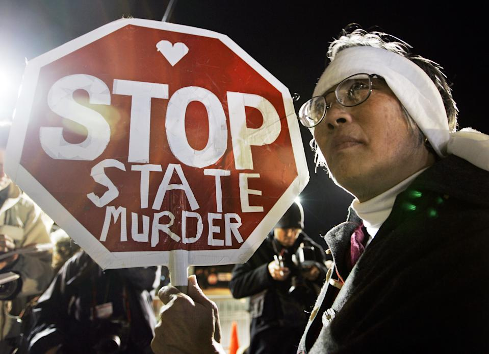 """FILE - In this Dec. 12, 2005, file photo, Barbara Chan protests the execution of Stanley """"Tookie"""" Williams, the founder of the Crips gang, outside of San Quentin State Prison in San Quentin, Calif. Williams was executed early Dec. 13. California voters face opposite choices to fix the state's broken death penalty. They can repeal capital punishment in November or reform it so convicted murderers are actually executed. (AP Photo/Eric Risberg, File)"""