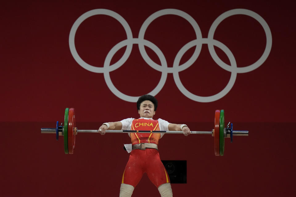 Hou Zhihui of China competes in the women's 49kg weightlifting event, at the 2020 Summer Olympics, Saturday, July 24, 2021, in Tokyo, Japan. (AP Photo/Luca Bruno)