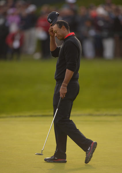 Tiger Woods takes his cap off after missing a putt on the 18th green and losing the match to Zach Johnson on a playoff to during the final round of the Northwestern Mutual World Challenge golf tournament at Sherwood Country Club, Sunday, Dec. 8, 2013, in Thousand Oaks, Calif. (AP Photo/Mark J. Terrill)