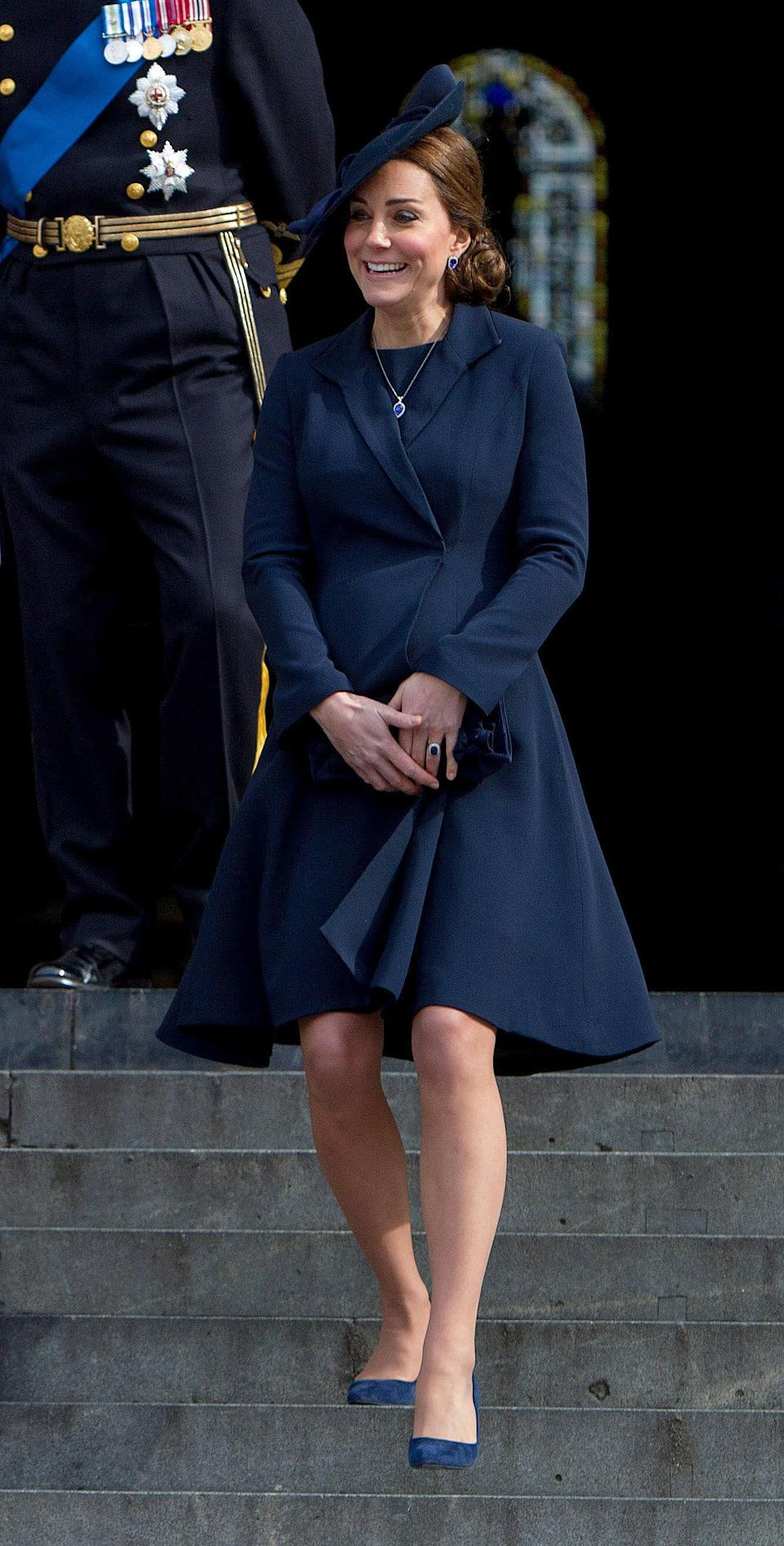 <p>The duchess was all smiles in a navy coat by Beulah London paired with blue suede heels.<br>(Photo: PA) </p>