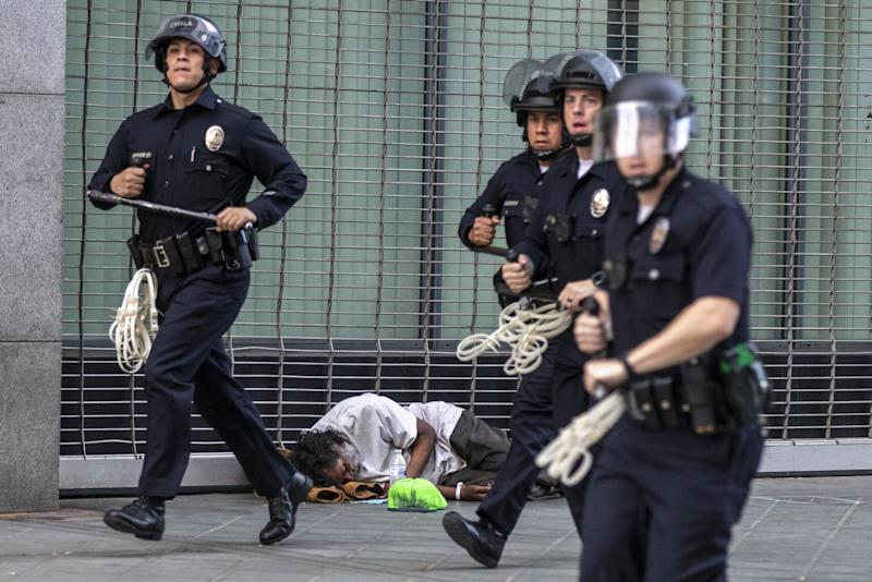 Los Angeles police officers rush to arrest dozens of protesters who were violating curfew laws on Broadway on Tuesday.