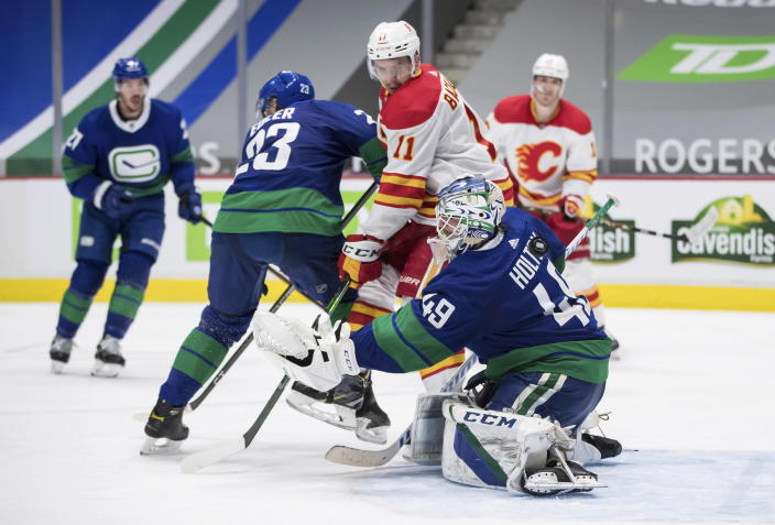 Calgary Flames' Mikael Backlund (11), of Sweden, deflects the puck wide of the goal behind Vancouver Canucks goalie Braden Holtby (49) as Alexander Edler (23), of Sweden, defends during the third period of an NHL hockey game, Sunday, May 16, 2021, in Vancouver, British Columbia. (Darryl Dyck/The Canadian Press via AP)