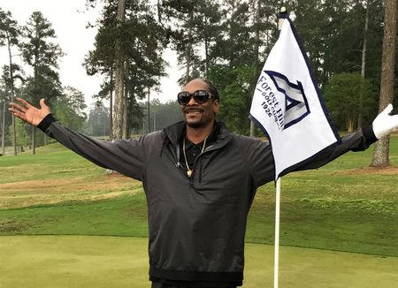 Rapper Snoop Dogg reacts after take a few practice swings at a golf course in Augusta