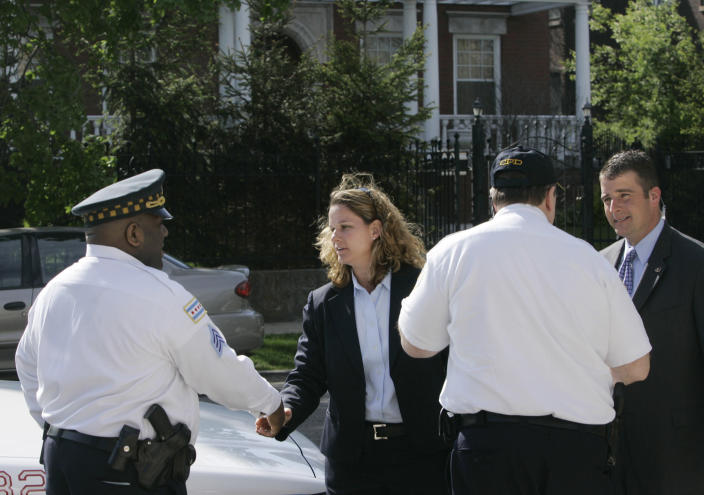 FILE - In this Thursday, May 3, 2007 file photo, a female Secret Service agent introduces herself to Chicago Police outside the home of Democratic Sen. Barack Obama, in Chicago's Hyde Park neighborhood. The Secret Service said Thursday that Obama was being placed under its protection, the earliest ever for a presidential candidate. The Secret Service has been tarnished by a prostitution scandal that erupted April 13, 2012 in Colombia involving 12 Secret Service agents, officers and supervisors and 12 more enlisted military personnel ahead of President Barack Obama's visit there for the Summit of the Americas. (AP Photo/Charles Rex Arbogast)