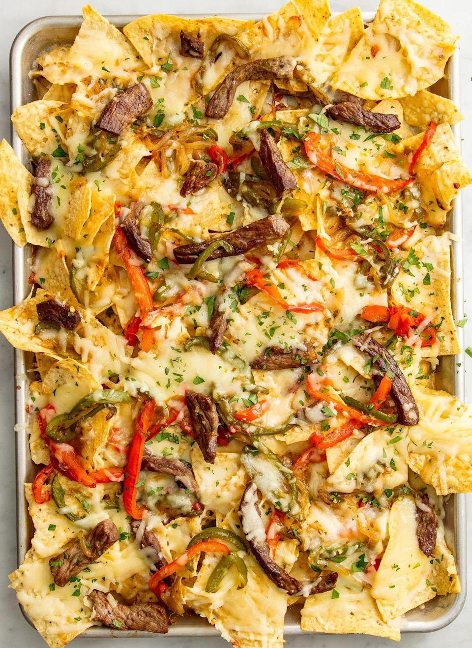 """<p>Proof that everything is better in nacho form.</p><p>Get the recipe from <a href=""""https://www.delish.com/cooking/recipe-ideas/recipes/a51879/philly-cheesesteak-nachos-recipe/"""" rel=""""nofollow noopener"""" target=""""_blank"""" data-ylk=""""slk:Delish"""" class=""""link rapid-noclick-resp"""">Delish</a>.</p>"""