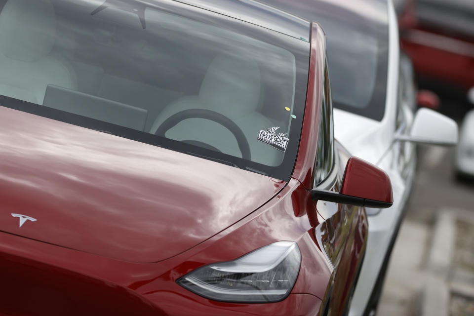 In this Sunday, June 28, 2020, photograph, a long line of unsold 2020 Model Y sports-utility vehicles sits at a Tesla dealership in Littleton, Colo. (AP Photo/David Zalubowski)