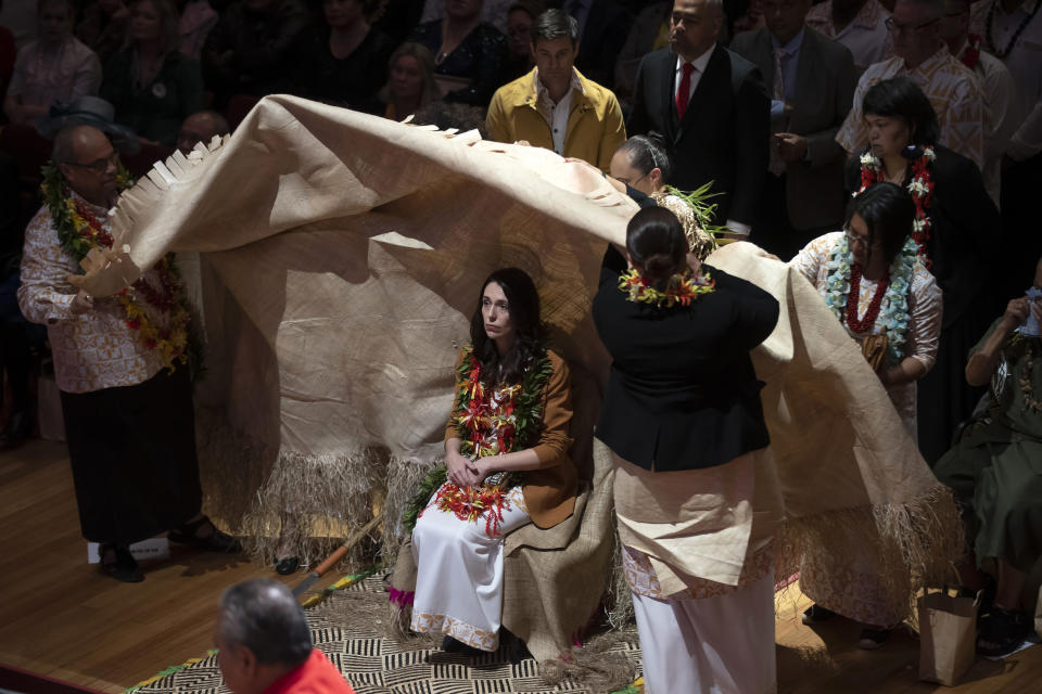 New Zealand Prime Minister Jacinda Ardern, center, is covered during a ceremony in Auckland, Sunday, Aug. 1, 2021, to formally apologize for a racially charged part of the nation's history known as the Dawn Raids. The Dawn Raids are known as the time when the Pasifika people were targeted for deportation in the mid-1970s during aggressive home raids by authorities to find, convict and deport visa overstayers. (Brett Phibbs/New Zealand Herald via AP)