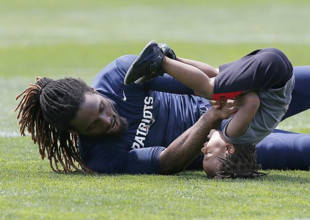 New England Patriots running back Brandon Bolden plays with his son Brycen, 3, following NFL football training camp in Foxborough, Mass., Saturday, July 26, 2014. (AP Photo)